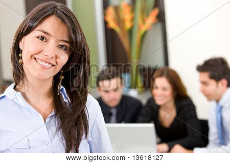 busines woman in an office smiling with her team behind her