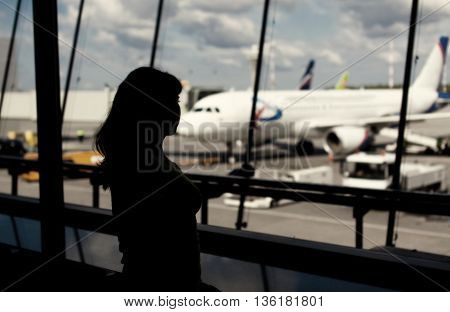 Toned photo of silhouette of woman looking through window in the airport
