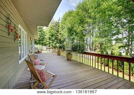 Wooden Walkout Deck With Chairs And Flower Pots .