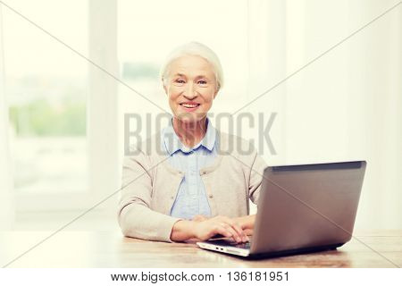 technology, age and people concept - happy senior woman with laptop computer at home