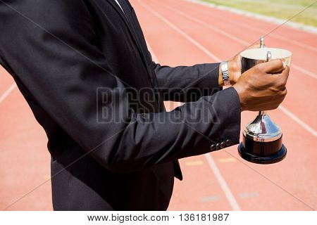 Mid section of businessman holding winning trophy on running track