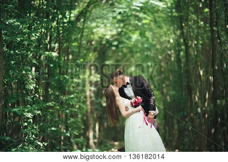 Young wedding couple, bride and groom posing on a railway track.