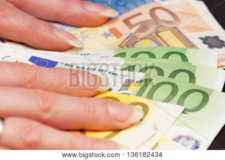 Beautiful woman's hands holding several euro banknotes