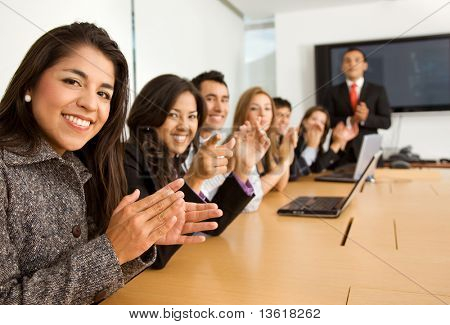 business success team in an office clapping a presentation