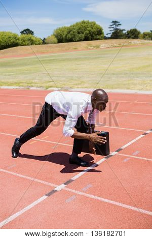 Businessman with briefcase ready to run on running track