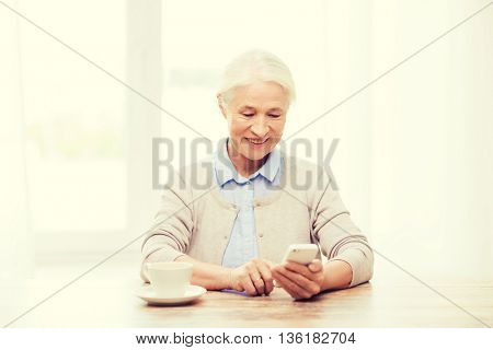 technology, communication age and people concept - happy senior woman with smartphone and coffee sitting at table and texting message at home