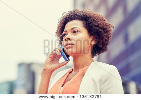 business, communication, technology and people concept - young african american businesswoman calling on smartphone in city