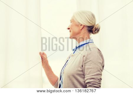 age and people concept - happy smiling senior woman looking through window at home