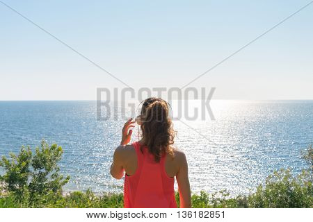 Sporty Girl with headphones and a red tank top looking at the sea in the summer the view from the back