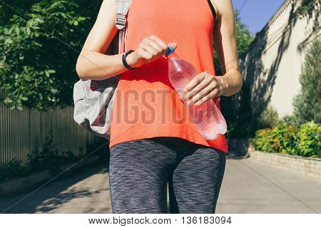 Girl in sportswear with backpack holding a bottle of cold water. Woman walking on the street in summer.