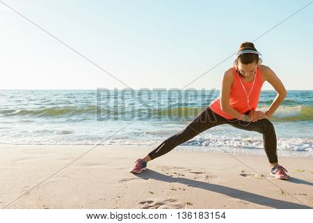Slim athletic girl in a red t-shirt has been stretching in the morning on the beach in the sunshine. Concept sports lifestyle space for text.