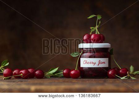 Jar of cherry jam with fresh cherries beside it
