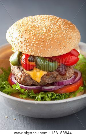homemade cheese burger with peppers tomato onion