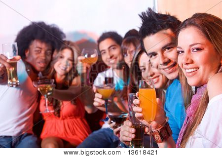 group of happy friends smiling in a bar or a nightclub