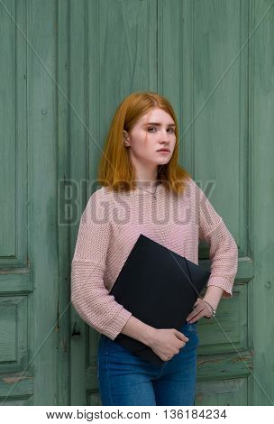 Girl Standing With A Black Folder In Hands