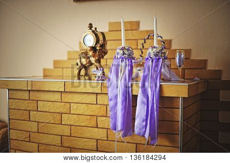 Wedding Candles With Purple Ribbons On Fireplace