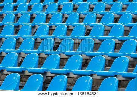 Background of empty plastic blue seats in a stadium