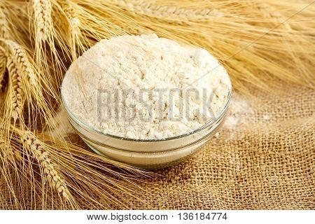 bowl of flour and wheat on burlap sack