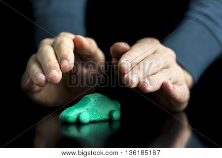 Car insurance concept - male hands making protective gesture over a green car made of play dough on black desk with reflection. Over black background.