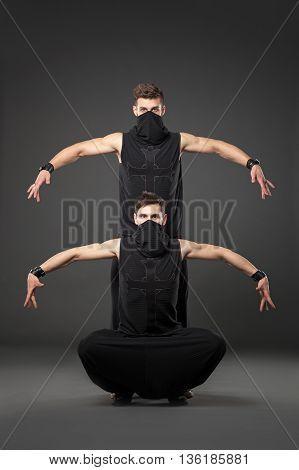 Two Male Dancers Posing In Ninja Costumes On Dark Gray Background.