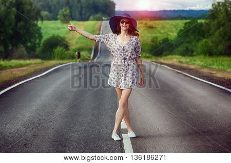 young girl travels on the highway hitchhiking