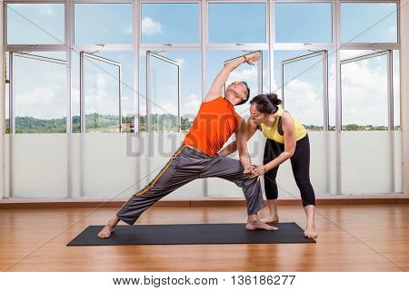 Yoga Instructor Guiding Student Perform Extended Side Angle Pose