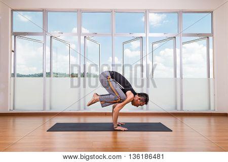 Yoga Practitioner Performing Crane Or Crow Pose Or Bakasana Pose
