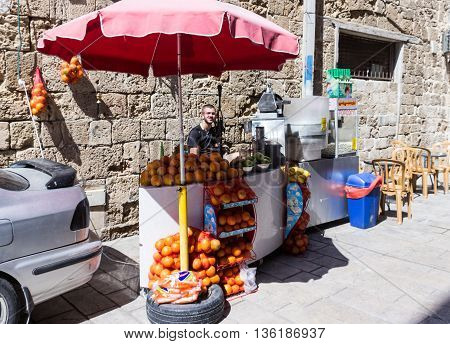 Acre Israel - May 28 2016: Street vendor of fresh fruit fresh juice and popcorn awaiting buyers in old city in Akre Israel