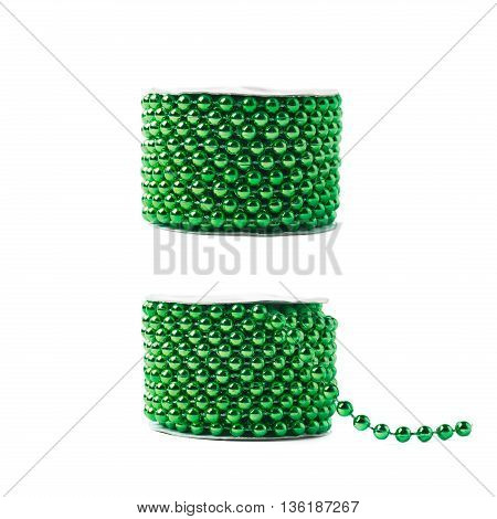 Small green beads garland thread on a reel isolated over the white background, set of two different foreshortenings