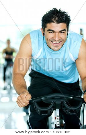 Man Smiling While Cycling In A Gym