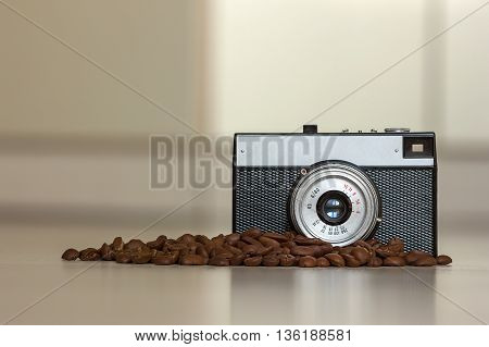 Little old fashioned vintage camera and coffee beanes on blurred background