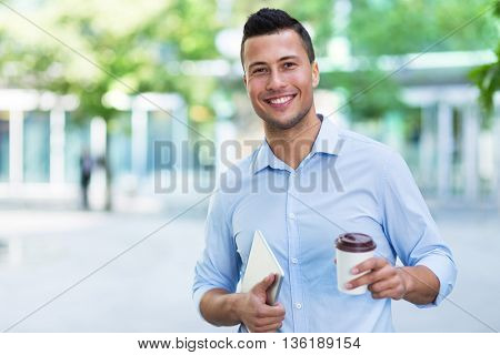 Young man holding coffee outdoors