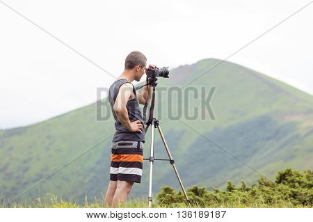 Photographer with a camera on tripod taking picture of mountains
