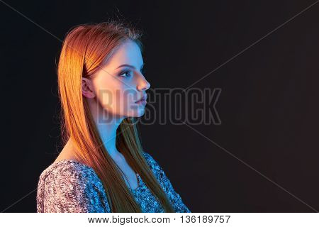 Profile portrait of beautiful red haired girl looking forward over dark background, in colorful lighting, with copy space