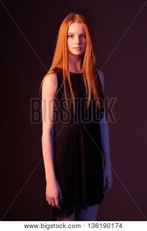 Fashion portrait of beautiful red haired fashion model girl with long hair in black dress, tonned image