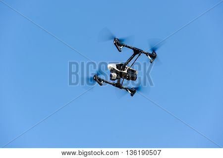 Drone with camera hovering in blue sky
