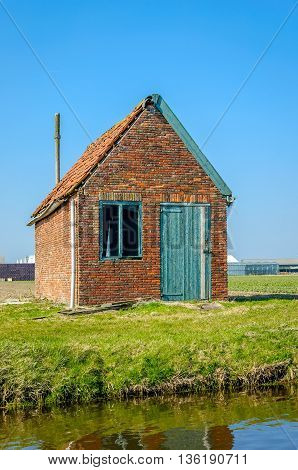 Dilapidated old barn on the banks of a Dutch stream on a sunny day in springtime.