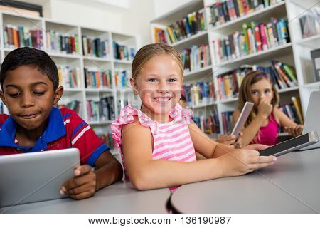 Portrait of smiling girl with tablet pc in library