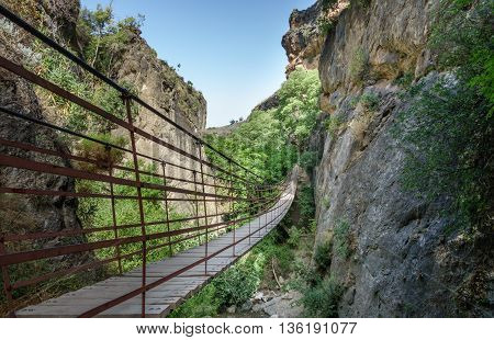 Wide angle view of rope bridge over a canyon in Cahorros, Granada, Andalusia, Spain