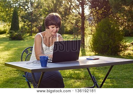 Pretty middle-aged woman is working on laptop sitting in beautiful summer garden