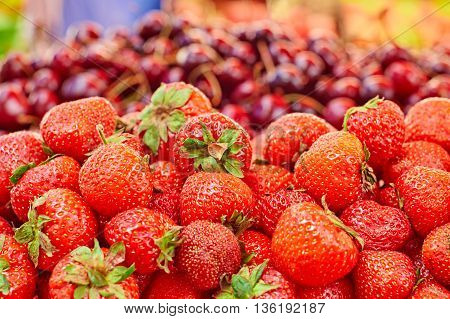 Сounter on the market: strawberry in the foreground and cherries in the background
