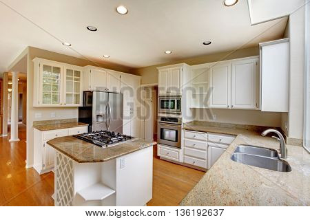 Classic American Kitchen Interior With White Cabinets And Built-in Stainless Steel Fridge.