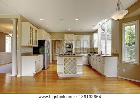 Small Classic American Kitchen Interior With White Cabinets And Hardwood Floor..