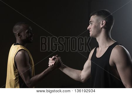 Portrait of basketball players shaking hands on a gym