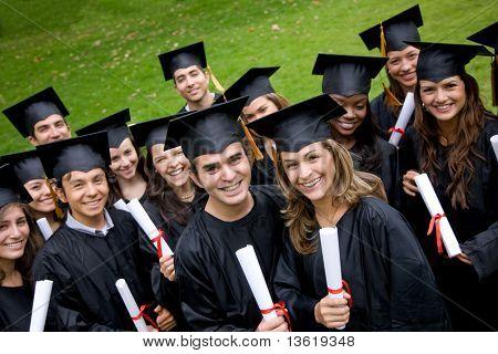 Graduierung Studenten im Park suchen glücklich