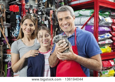 Happy Salesman Holding Rabbit While Standing With Family