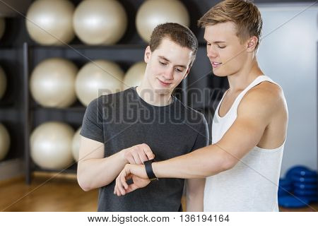 Handsome Friends Checking Pedometer In Gym