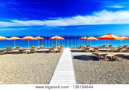 White wooden walkway on beach including umbrellas with deck chairs. Aegean Sea. Greece Rhodes. pebble beach