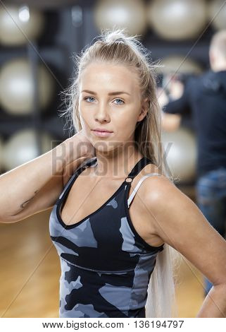 Confident Young Woman Touching Neck In Gym
