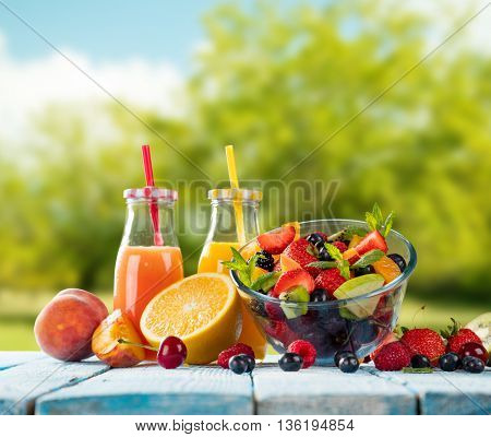 Fresh glasses of juice and salad with fruit mix placed on wooden planks. blur garden on background. Concept of healthy eating, antioxidants and summer cocktails.